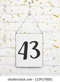forty three years old birthday congratulations text with golden confetti sign white brick background