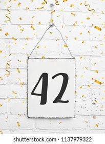 forty two years old birthday congratulations text with golden confetti sign white brick background