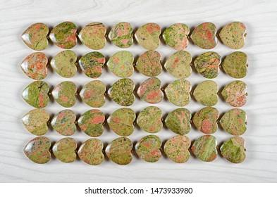Forty unakite heart-shaped stones are stowed five rows. Eight pieces in each one. Top view.