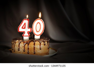 Forty years anniversary. Birthday chocolate cake with white burning candles in the form of number Forty. Dark background with black cloth