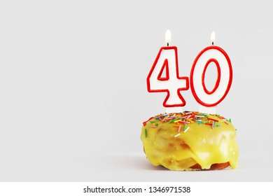 Forty years anniversary. Birthday cupcake with white burning candles with red border in the form of number Forty. Light gray background with copy space