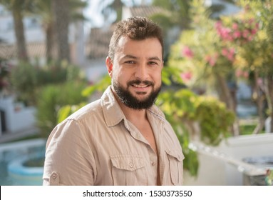 Forty years old bearded man portrait in garden looking at camera and smirking