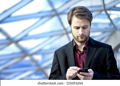 Forty years old businessman standing inside modern office building looking on a mobile phone