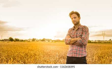 Forty years old caucasian farmer in plaid shirt standing proud in front of wheat field. Agriculture - country outdoor scenery, warm sunset light.