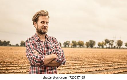Vierzig Jahre alter Kaukasier Bauer in gepolstertem Hemd steht stolz vor dem Zwiebelfeld. Landwirtschaft - Landschaft im Freien (Landschaft).