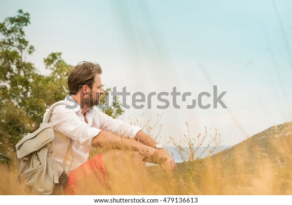Forty years old caucasian tourist man taking a break while mountain trip. Meadow and hills as background. Summer vacation (holiday), traveling and adventure.