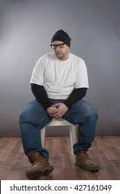 Forty years old man wearing white t-shirt black frame glasses and black skull hat,blue jeans sitting on white chair looking depressed and for someone else help