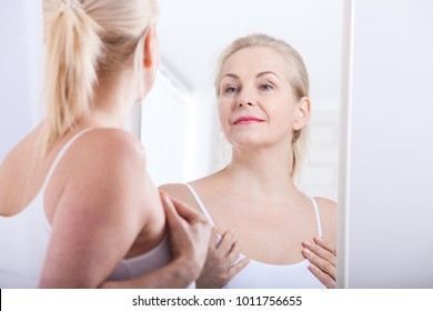 Forty years old woman looking at wrinkles in mirror. Plastic surgery and collagen injections. Makeup. Macro face. Selective face