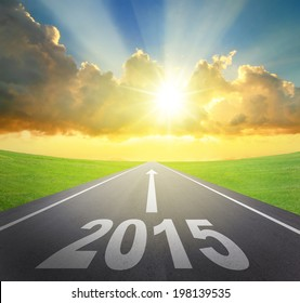 Forward to 2015 new year concept , asphalt road with arrow , date and beautiful sunset and sunshine