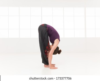 forward bending yoga pose, shown by younf female, dreesed colorful, on white background, side view in studio