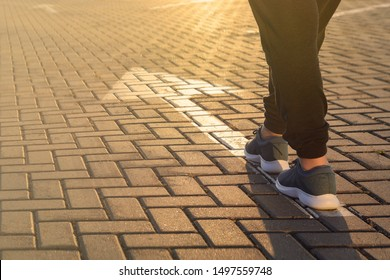 Forward moving. Feet on road arrow in the rays of setting sun
