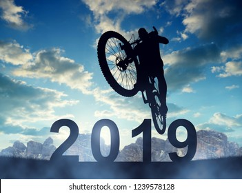 Forward to the New Year 2019. Cyclist jumping on the bicycle at sunset.