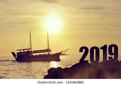Forward to the New Year 2019.Silhouette of a ship at sea in the sunset.
