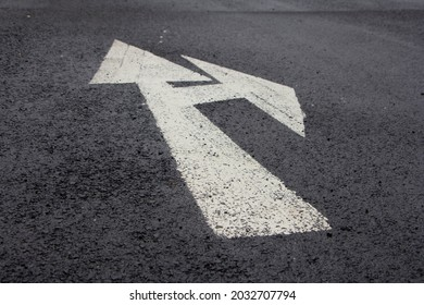 Forward and right direction arrow on asphaltic road captured in inclined view