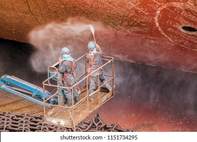 Forward Ship in Floating dock worker during Cleaning surface of the deck with high pressure water, process of maintenance, On sherry picker car an Removed rust first before sand blasting and painting