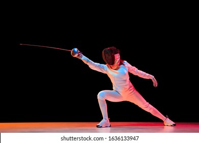 Forward. Teen girl in fencing costume with sword in hand isolated on black background, neon light. Young model practicing and training in motion, action. Copyspace. Sport, youth, healthy lifestyle.