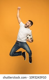 Forward to the victory.The young man as soccer football player jumping and kicking the ball at studio on a yellow background. Football fan and world championship concept. Human emotions concepts