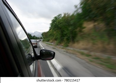 Forward view from car driving on highway in line of cars at high speed. Blurred roadside, focus on mirror.
