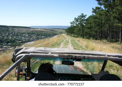 Forward view from open cab of off road car moving on mountain country road.