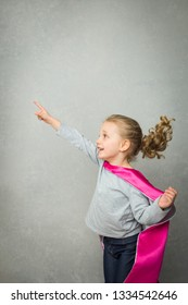 Forward-oriented pose by little girl playing superhero