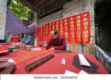 FOSHAN, CHINA - FEBRUARY 10, 2018: A calligrapher is writing Spring Festival Couplets for people.  It is the most common and important custom when celebrating Chinese New Year.