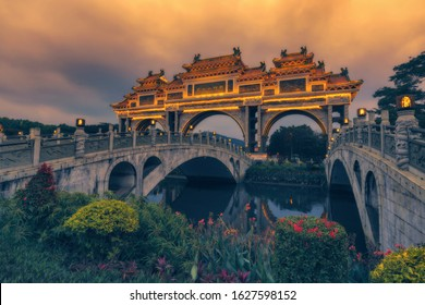 Foshan city, China. City park gates in the dark, water channel and flowers. TRANSLATION: the park name, Shunfengshan park.