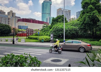 Foshan city, Guangdong province, China-May 21, 2018: A driving road with a sedan and motor scooter at the foreground and 54-floor cylindrical tower of Baihua Plaza at the background.