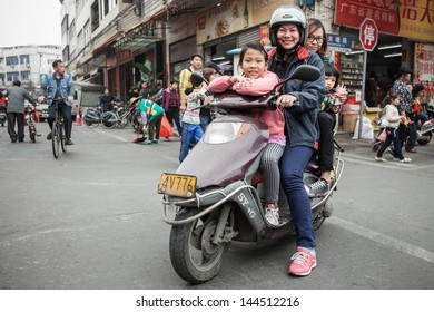 FOSHAN, GUANGDONG/CHINA - MARCH 16: Four unidentified people share the same scooter. Shunde District of Foshan City, Guangdong Province in Southern China on March 16th, 2013.