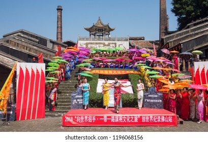 Foshan,China-October 1, 2018:To celebrate the National Day holiday, dozens of women wearing qipao and carrying umbrellas showed off the traditional Chinese culture to tourists at the ceramic ancient k