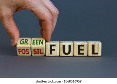 From fossil to green fuel. Male hand turns cubes and changes the words 'fossil fuel' to 'green fuel'. Beautiful grey background. Business and green fuel concept. Copy space.
