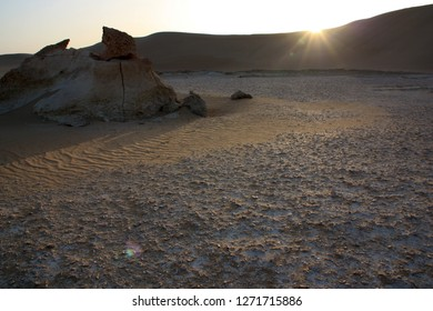 Fossilized sea life, rock and chalk formations surrounded by beautiful sand dunes in the Sahara desert near Siwa Oasis in Western Egypt with a low evening sun just overhead the ridge of a sand dune