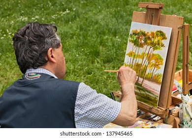 """FOSSO GHIAIA, RAVENNA, ITALY - APRIL 28: painter at work painting the pine forest during the festival """"Sagra del pinolo"""" on April 28, 2013 in Fosso Ghiaia, Ravenna, Italy"""