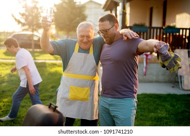 Fother and son are holding each other hugged with one arm while holding others up and singing in front of a grill.