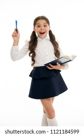 Found out about. Child school uniform smart kid happy with homework. Child girl happy school uniform clothes holds book and pen. Girl cute surprised face found out important idea, white background.