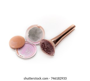 foundation bottle, compact powder, concealer pencil, makeup brushes and cosmetic sponges on gray textured surface