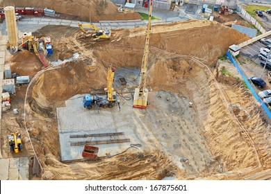 Foundation ditch with construction machinery at construction site, high angle view