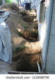 Foundation lifting. Repair and lifting of a foundation that has settled.  Brackets, equipment, holes, dirt