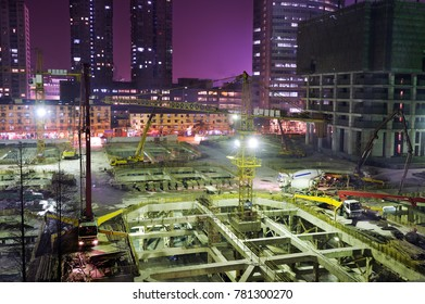 Foundation with parking level, construction of new building. New tower construction. Crane, trucks and people warking at night. In Shanghai construction sites are active day and night