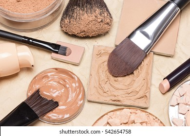 Foundation, powder, concealer pencil with make up brushes on crumpled paper. Makeup products to even out skin tone and complexion