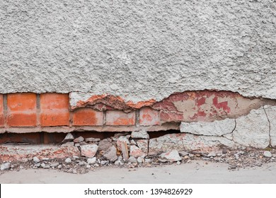 The foundation of a residential building is gradually collapsing. Cracks in the foundation. Plaster falling off of a brick wall due to the impact of weather factors.