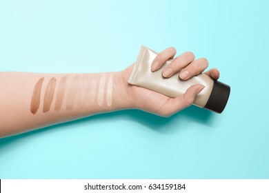 Foundation swatches on hand, woman holding makeup tube, testing different shades