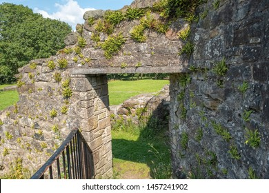 The foundations of some ancient Scottish Ruins with an old stone doorway and arch.