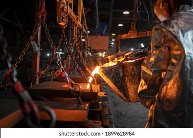 Foundry casting and process of pouring liquid molten iron. Metallurgy and heavy industry.