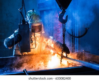 Foundry worker with special protective suit quenching casts in oil bath