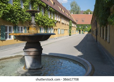 Fountain and apartments in the Fuggerei in Augsburg