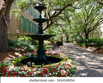 Fountain and birdbath surrounded by colorful flowers on a shady walkway on the campus of the historic College of Charleston in Charleston, South Carolina; horizontal