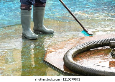 fountain cleaner on the street, washes the surface of the fountain inside where water flows, hose and brush for cleaning dirt