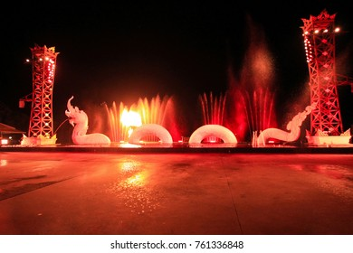 Fountain dance show in front of dragon statue in Phuket, red colors