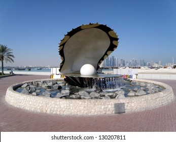 A fountain featuring an oyster with a gigantic pearl inside with the Doha skyline behind it..