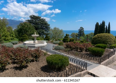 fountain in the garden in front of the white Livadia Palace in Yalta, Crimea on a beautiful background with the sea and clouds